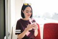 Young, beautiful girl passenger in the moving bus using social network on her smartphone and looking - PhotoDune Item for Sale