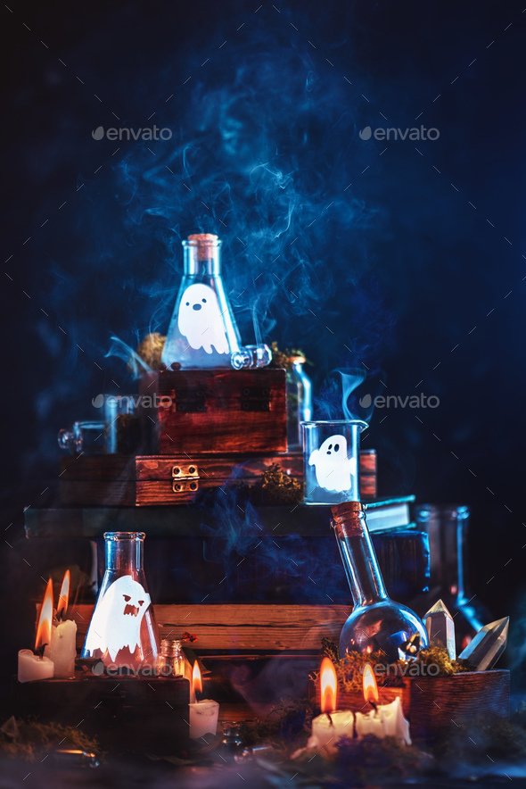 Little ghosts in glass jars. Halloween concept on a dark background with a stack of magical books - Stock Photo - Images