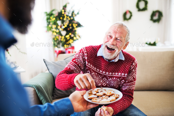 A man giving biscuits to his senior father at home at Christmas time. - Stock Photo - Images