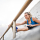 Young sporty woman runner with earphones stretching on the beach outside. - PhotoDune Item for Sale