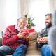 A senior father and adult son with a present sitting on a sofa at Christmas time. - PhotoDune Item for Sale