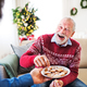 A man giving biscuits to his senior father at home at Christmas time. - PhotoDune Item for Sale