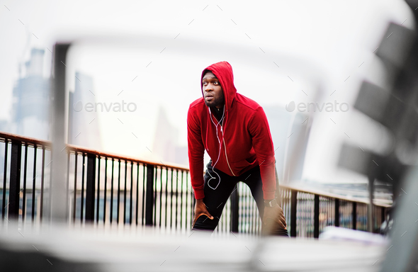 A black man runner with earphones and hood on his head in a city, resting. - Stock Photo - Images