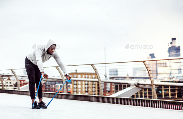 Young black sportsman exercising with elastic rubber bands in London. - Stock Photo - Images
