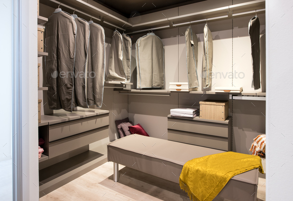 Interior of a walk in closet with hanging clothes - Stock Photo - Images
