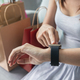 Young asian woman with shopping bag using smart watch at home - PhotoDune Item for Sale