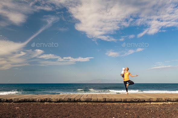 Life balance. Yoga girl meditating and relaxing holding baby tod - Stock Photo - Images