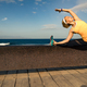 Woman runner stretching at the seaside on sunny summer day - PhotoDune Item for Sale
