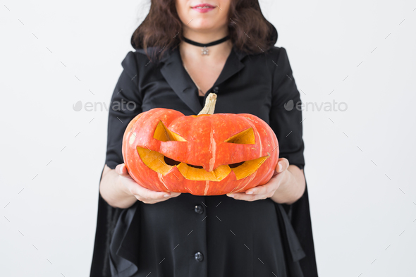 Close up of gothic woman in halloween style clothes with pumpkin in hands - Stock Photo - Images
