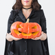Close up of gothic woman in halloween style clothes with pumpkin in hands - PhotoDune Item for Sale