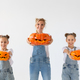Mother and her daughters twins holding Jack-O-Lantern pumpkin on Halloween  - PhotoDune Item for Sale
