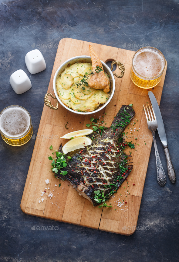 Delicious baked flounder with potato gratin and beer, top view. - Stock Photo - Images