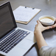 Young woman drinking coffee while working on laptop in cafe - PhotoDune Item for Sale
