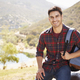 Young Hispanic man smiling during mountain hike, portrait - PhotoDune Item for Sale
