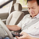 Senior man in car using his smartphone while driving - PhotoDune Item for Sale