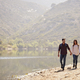 Young couple walk holding hands by a mountain lake - PhotoDune Item for Sale