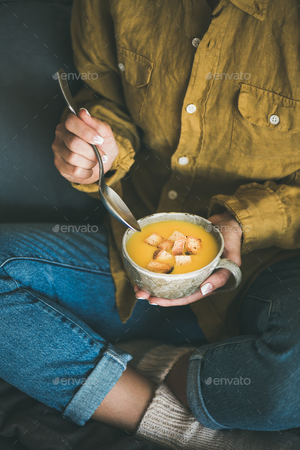 Woman sitting and eating warming pumpkin soup from mug - Stock Photo - Images