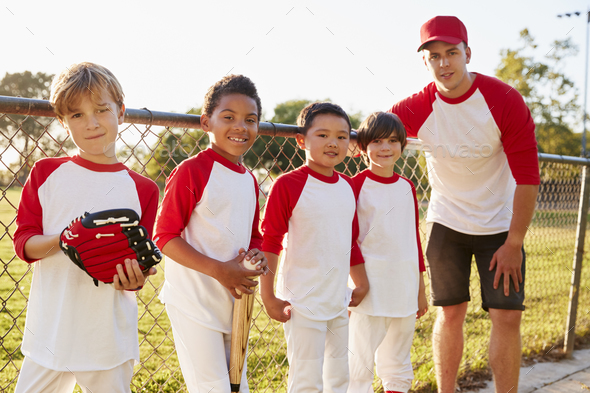 Coach and young boys in a baseball team looking to camera - Stock Photo - Images