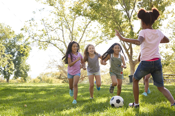 Four young girlfriends running after a football in the park - Stock Photo - Images