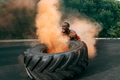 Handsome muscular man flipping big tire outdoor. - PhotoDune Item for Sale