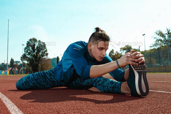 Man runner stretching legs preparing for run training on stadium tracks doing warm-up - Stock Photo - Images