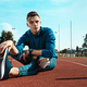 Man runner stretching legs preparing for run training on stadium tracks doing warm-up - PhotoDune Item for Sale