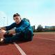 Man runner stretching legs preparing for run training on stadium tracks doing warm-up - PhotoDune Item for Sale