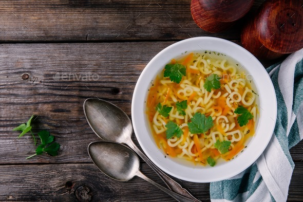 Homemade Chicken and Alphabet Soup with carrots and parsley in bowl - Stock Photo - Images