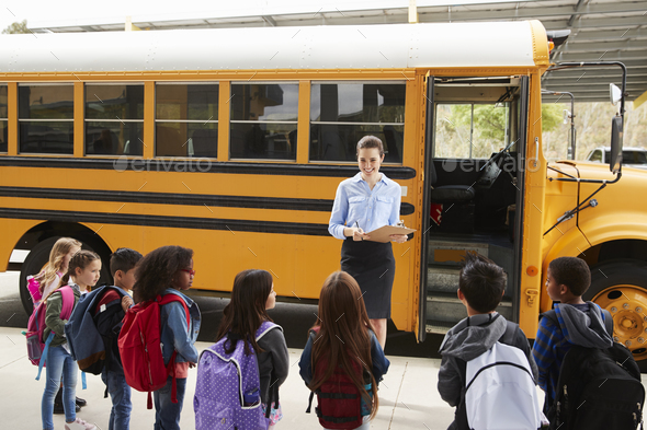 Teacher taking a register of school kids by school bus - Stock Photo - Images