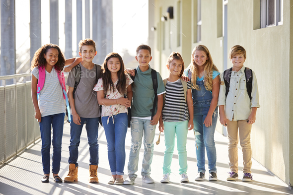 Elementary school kids stand in corridor looking at camera - Stock Photo - Images
