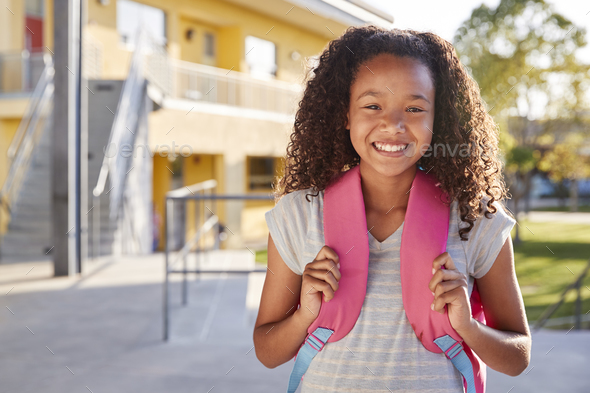 Portrait of smiling elementary school girl with her backpack - Stock Photo - Images