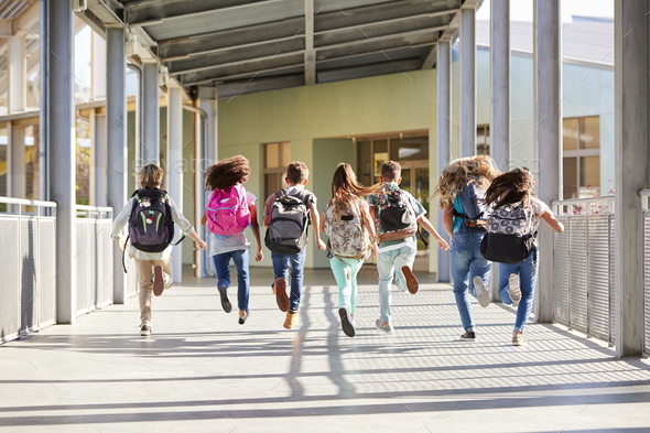 Elementary school kids running at school, back view close up - Stock Photo - Images