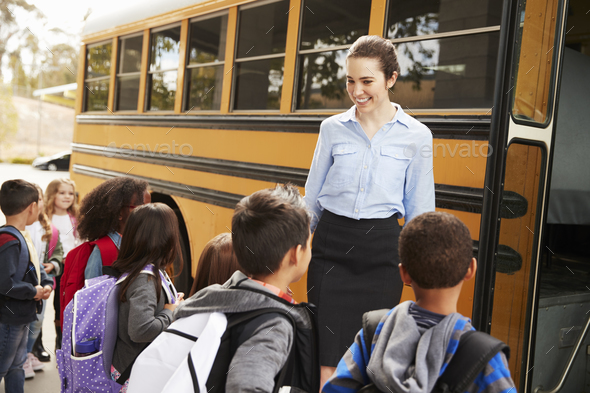 School teacher preparing kids to get on the school bus - Stock Photo - Images