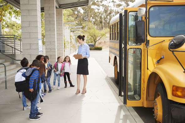Teacher talks to young school kids by school bus, side view - Stock Photo - Images