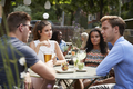 Friends Sitting At Table In Pub Garden Enjoying Drinks Together - PhotoDune Item for Sale