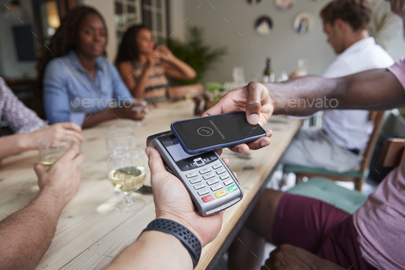 Close Up Of Customer In Restaurant Paying Bill With Contactless Phone App - Stock Photo - Images
