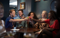 Group Of Young Friends Sitting Around Table And Making A Toast In Bar On Night Out - PhotoDune Item for Sale