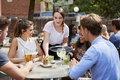 Waitress Serving Drinks To Group Of Friends Sitting At Table In Pub Garden Enjoying Drink Together - PhotoDune Item for Sale