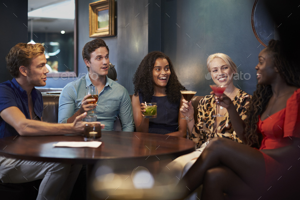 Group Of Young Friends Sitting Around Table In Bar Together On Night Out - Stock Photo - Images