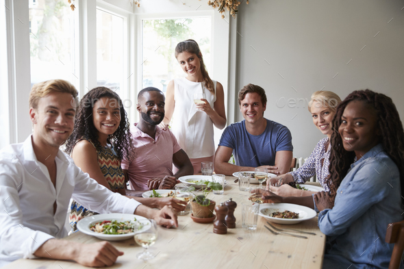 Portrait Of Friends Sitting At Table In Restaurant Enjoying Meal Together - Stock Photo - Images