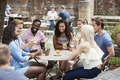 Friends Sitting At Table In Pub Garden Enjoying Drink Together - PhotoDune Item for Sale