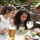 Friends Sitting At Table In Pub Garden Looking At Message On Mobile Phone - PhotoDune Item for Sale