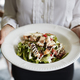 Close Up Of Waitress Holding Plate Of Chicken Salad In Restaurant - PhotoDune Item for Sale