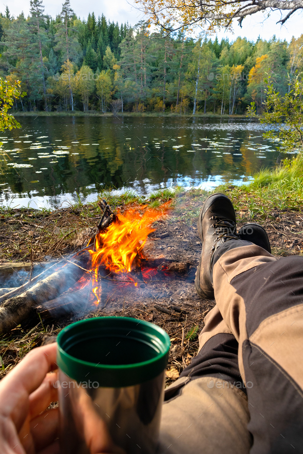 Man relaxing ourdoor by the fire in the forest with a coffee - Stock Photo - Images