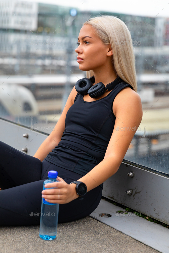 Thoughtful Runner Sitting On Bridge After Workout - Stock Photo - Images