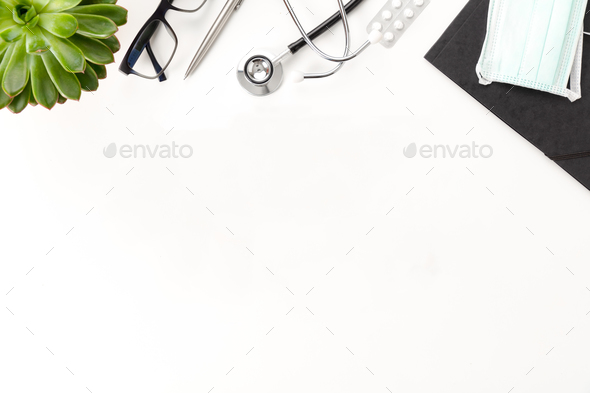 Doctors desk With Stethoscope And Eyeglasses By Plant On Table - Stock Photo - Images