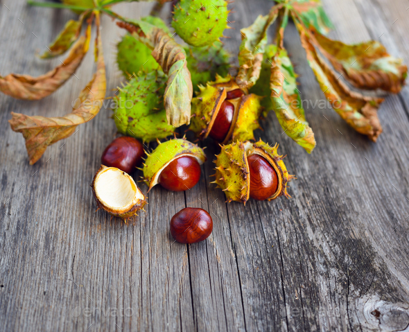 Chestnuts with dry leaves on old wooden background - Stock Photo - Images