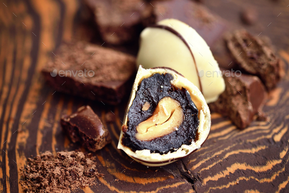 Handmade chocolate candies and pieces of chocolate on wooden bac - Stock Photo - Images