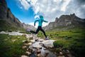 Woman trail runner jumping over small river on beautiful mountains - PhotoDune Item for Sale