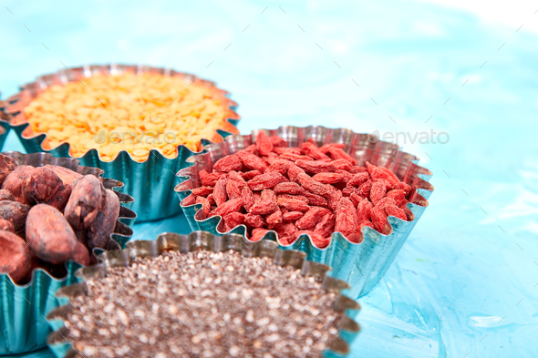 Various superfoods in small bowl on blue background - Stock Photo - Images